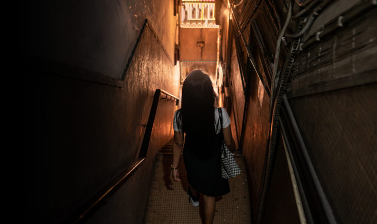 Windy Tanedo walking down the stairs of her boarding house in Macao