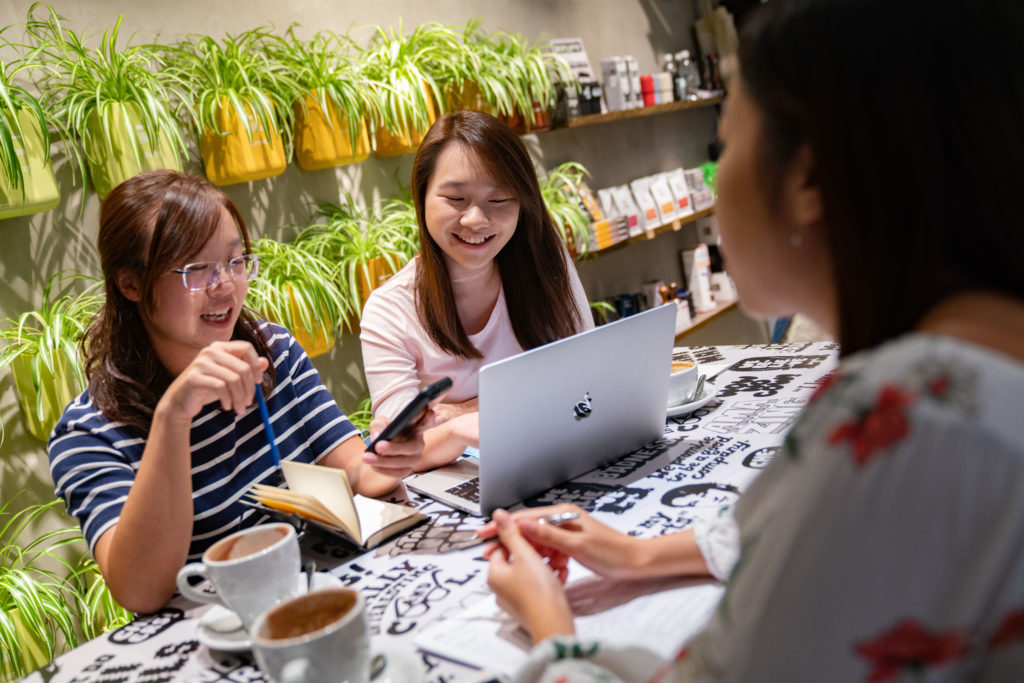 Joyce Fung, founder of MenstruAction, centre, Miranda Chu, publicity manager of MenstruAction, left, and Michelle Cheng, programme manager of MenstruAction discuss on an application for a grant during a meeting in cafe in Hong Kong on Friday, Nov 15, 2018.